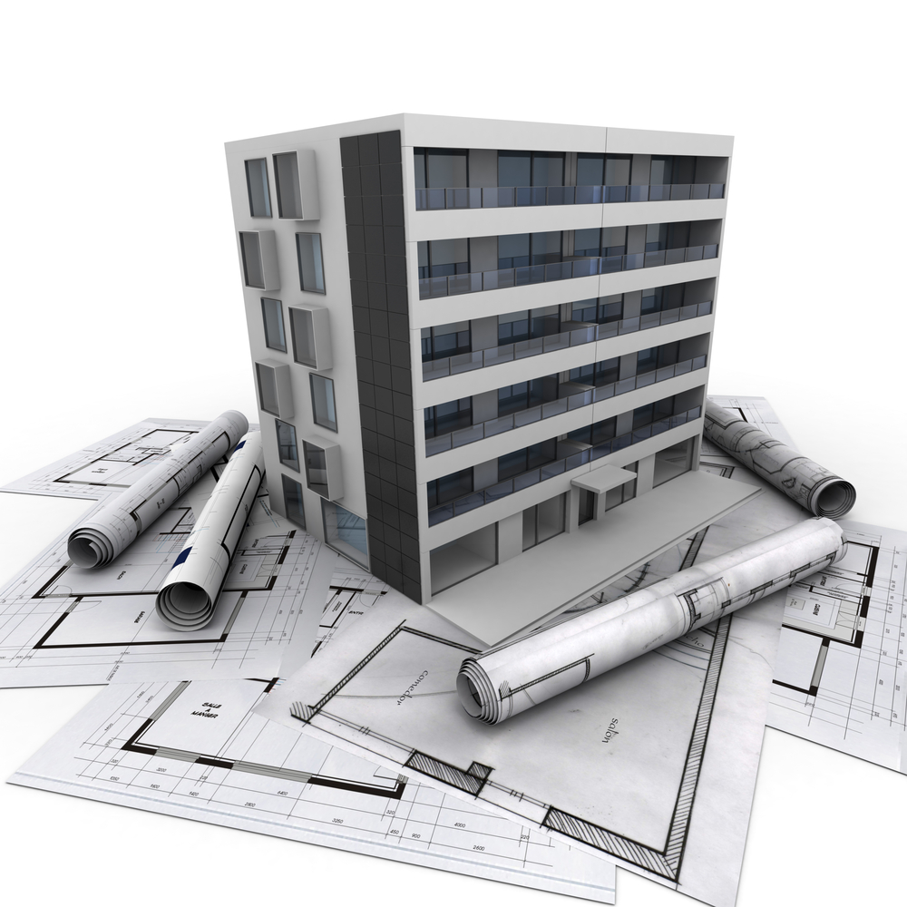 A commercial building on a pile of building plans.