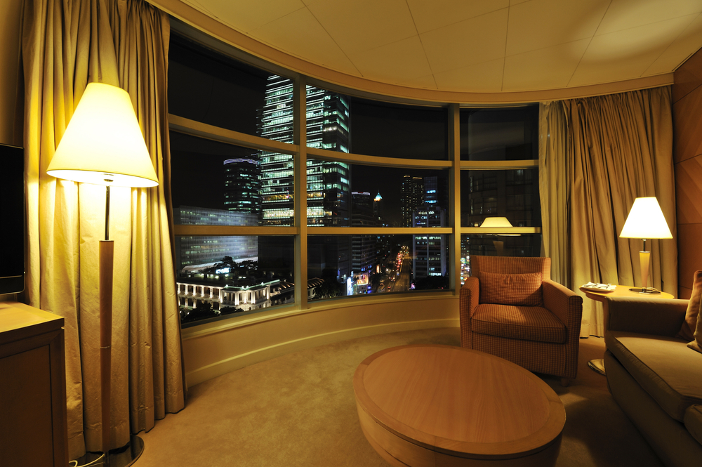 View of city skyline from inside a luxury hotel room.