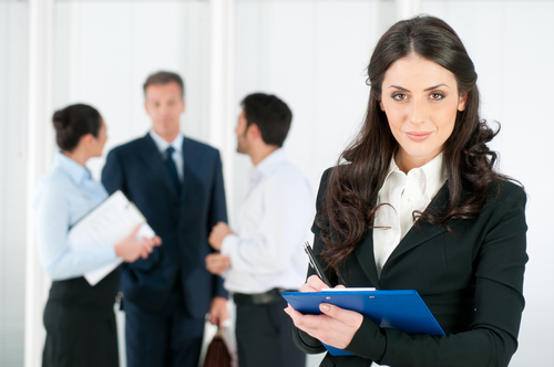 Woman with clipboard looking at camera with businessmen in the background.